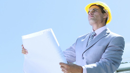 Engineer working outdoors with plans and a hard hat on Footage