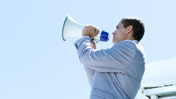 Young businessman shouting into a megaphone outdoo Footage
