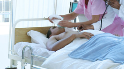 Doctor and nurse examining a patient in bed Footage