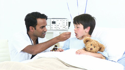 Doctor giving a little boy syrup in hospital Footage