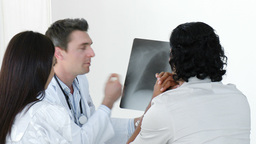 Doctor explaining an xray to a patient in office Footage