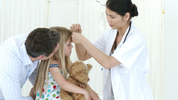Panorama of doctor taking little girls temperature Footage