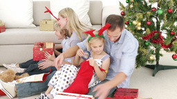 Family opening Christmas gifts in livingroom Footage