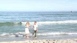 Couple running on the beach Footage