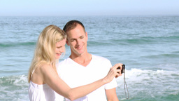 Panorama of couple on the beach taking photos of t Footage