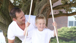 Close up of father and a son swinging in a park Footage