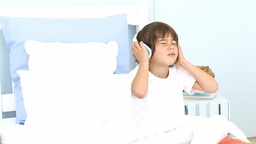 Little boy listening to music on his bed Footage