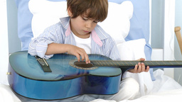 Close up of little boy playing guitar on bed Footage