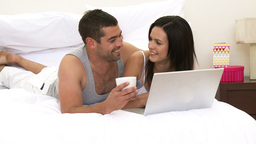 Couple in bed using a laptop Footage
