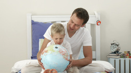 Father and son looking at a terrestrial globe Footage