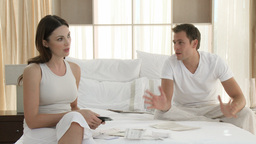 Couple arguing about bills on bed Live Action