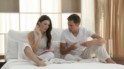 Couple checking bills on bed Footage