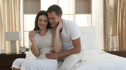 Happy couple looking at a positive pregnancy test  Footage