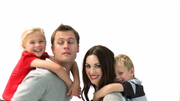 Happy parents giving children piggyback rides Footage