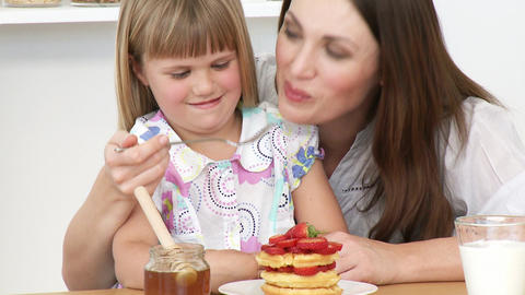 Close up of moher and daughter eating in the kitchen Live Action