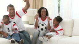 Family watching a football match at home Footage