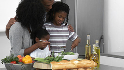 Panorama of AfroAmerican family making a salad at  Footage