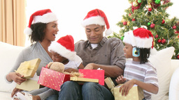 AfroAmerican family opening Christmas gifts on the Footage