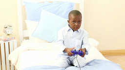 AfroAmerican little boy playing video games in his Footage