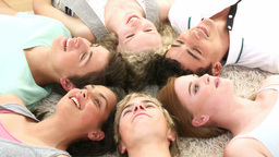 Teenagers with their heads together on the ground Footage