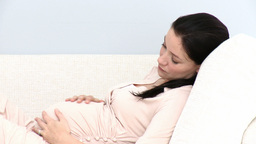 Pretty pregnant woman relaxing on sofa Footage