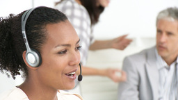 Smiling woman with headset on and her team Footage