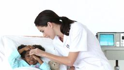 Attentive nurse checking little girls temperature Footage