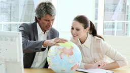 Charismatic business partners looking at a terrestrial globe Footage