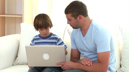 Concentrated father explaining his son how to use a laptop Animation