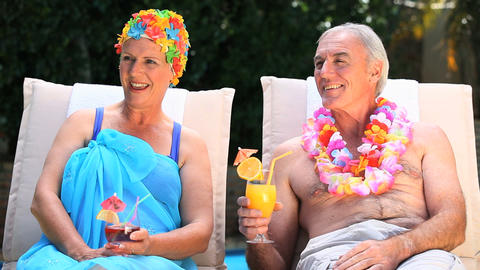 Old man and woman relaxing near the pool Footage