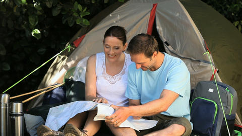 Couple looking at a map near a tent Footage