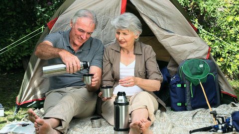 Aged couple drinking coffee sitting near a tent Footage