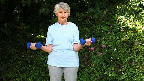 Old woman working her muscles with dumbbells Footage