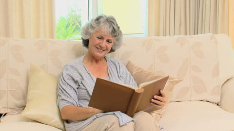 Old woman looking to an album and smiling at the camera Live Action