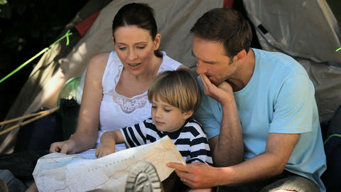 Family looking at a map near a tent Footage