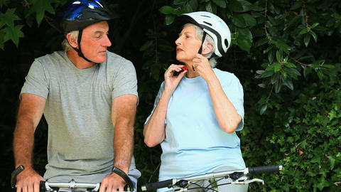 Elderly couple with bikes tying their helmets Footage