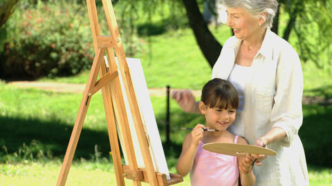 Young girl painting a canvas with grandmother Footage