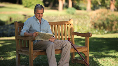Senior man reading a book sitting on a bench Footage