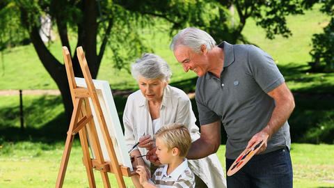 Young boy painting a canvas with grandparents Footage