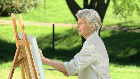 Elderly female painting a canvas Footage