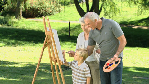 Grandparents and grandson painting a canvas Live Action