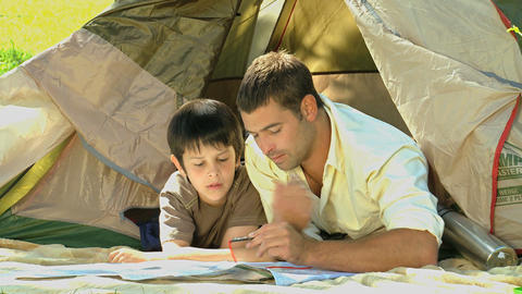 Father and son looking at a map near a tent Footage