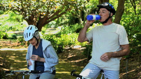 Elderly couple drinking after biking Footage