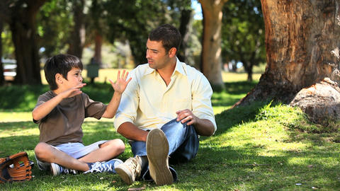 Father talking with his son sitting on the grass Footage