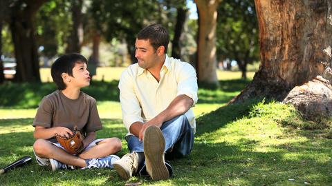 A boy talking with his dad sitting on the grass Footage