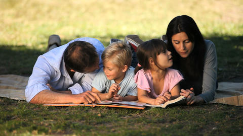 Family reading a book lying on the grass Footage