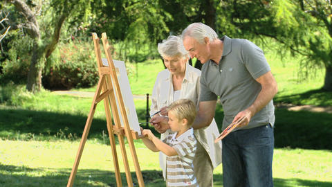 Boy painting a canvas with his grandparents Footage