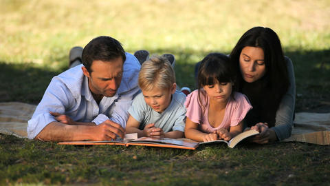 Family reading a book lying on a tablecloth Footage