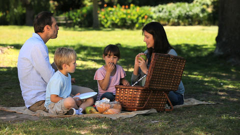 Parents enjoying a picnic with children on a table Footage