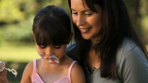 Mom and daughter blowing bubbles sitting on the gr Footage